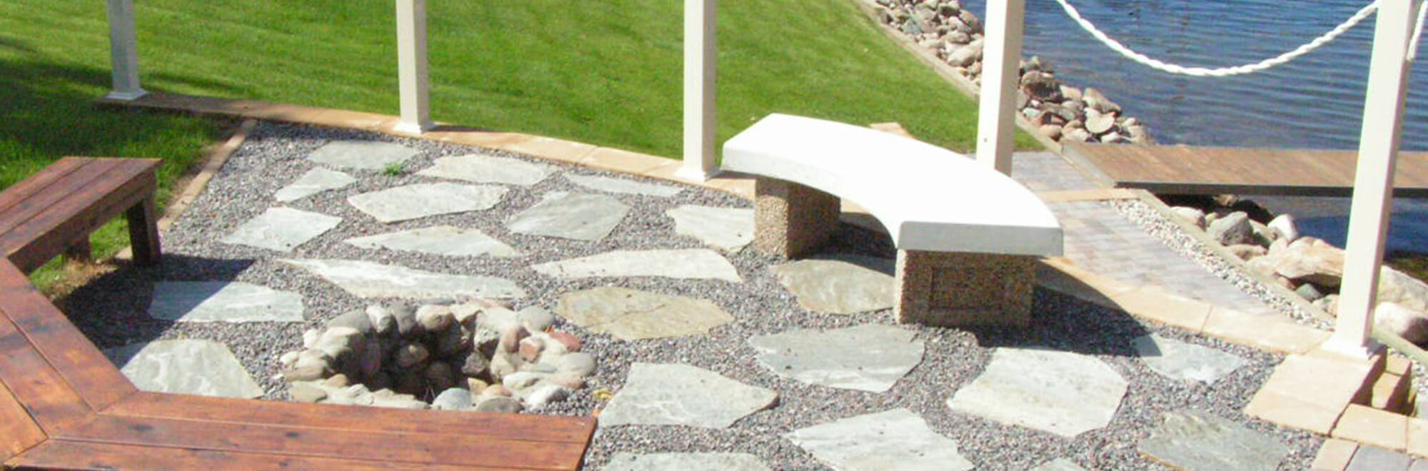Stone patio areat with curved seating benches around an in-ground fire pit