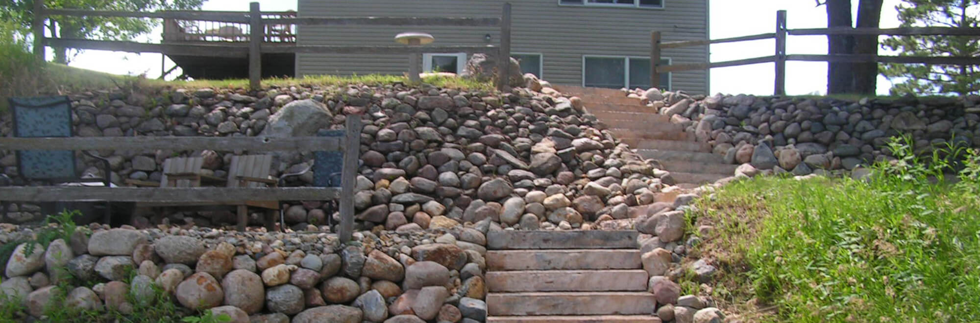 Steep grade in a residential backyard re-inforced with rip rap boulders and stone steps