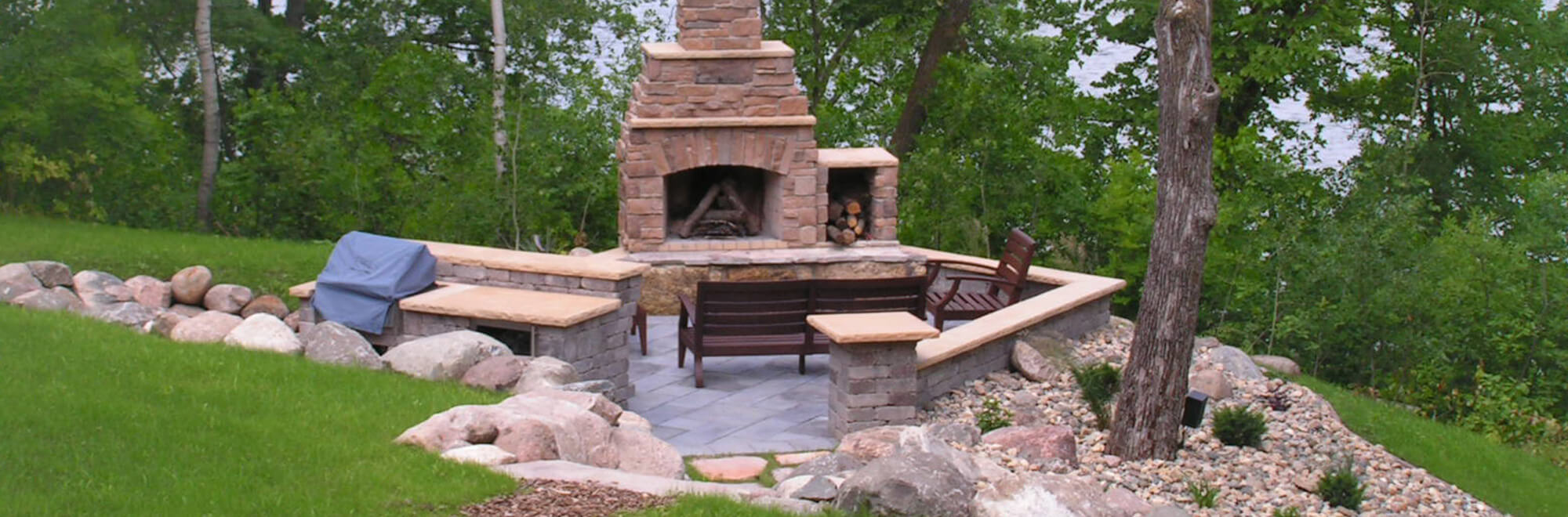 Outdoor living space in a backyard complete with paver patio, block seating wall, outdoor kitchen, and stone fireplace