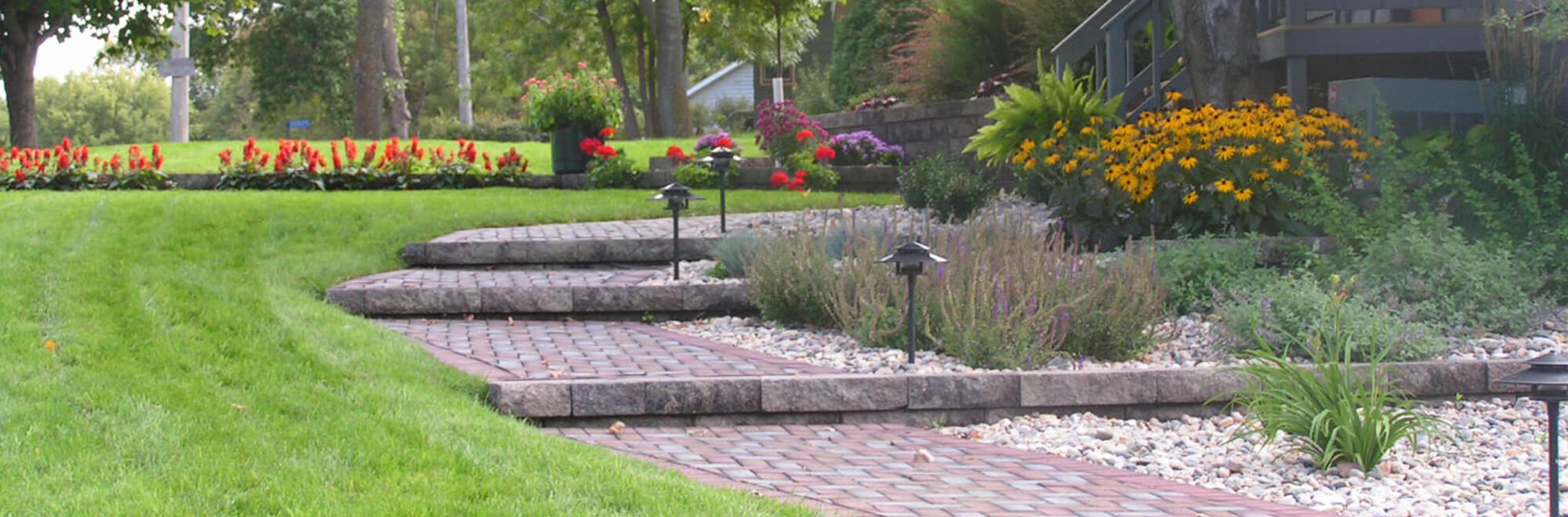 Home landscape complete with softscape flower gardens and stone paver steps