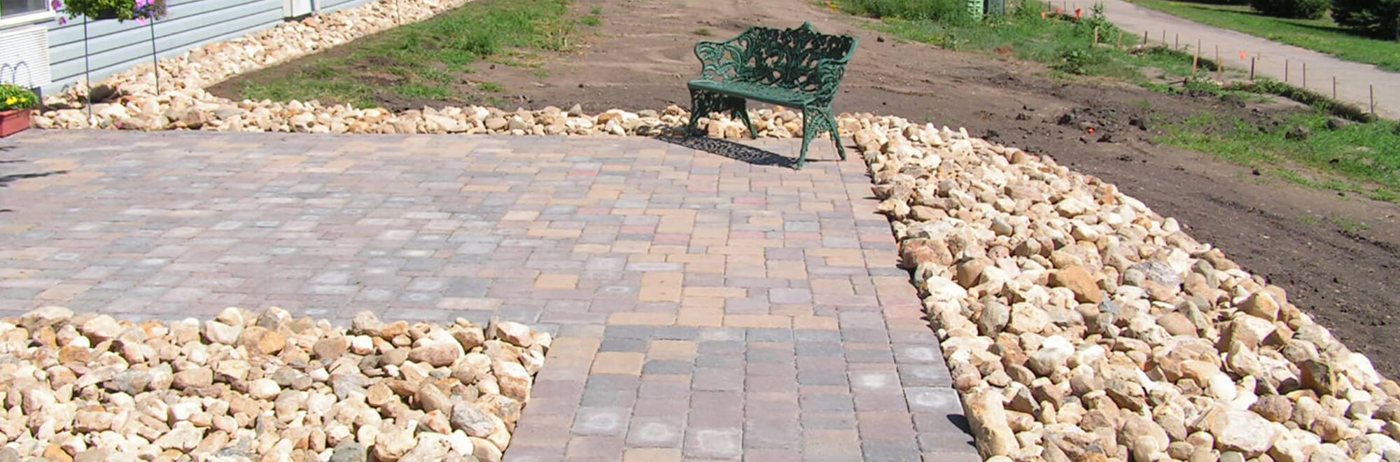 Paver patio and walking path installed along the side of a hoome and bordered with landscape rock